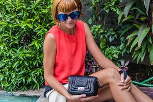 Fashionable young woman with stylish snakeskin python handbag, accessories, sunglasses, summer day, tropical Bali island, Indonesia.