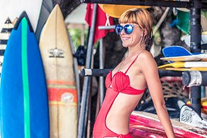 Young sexy girl in red swimsuit - surfer with surf board posing on the Nusa Dua beach, tropical Bali island, Indonesia. Family lifestyle, people water sport lessons and beach swimming activity on summer vacation.