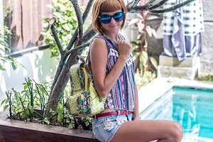 Outdoor fashion details, woman posing at the swimming pool, wearing luxury snakeskin python backpack, sunny bright colors, tropical island Bali, Indonesia.