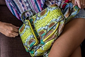 Outdoor fashion details, woman posing at the sofa, wearing luxury snakeskin python backpack, sunny bright colors, tropical island Bali, Indonesia.