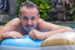 Portrait of handsome smiling man on the inflatable mattress in swimming pool at sunny day. Bali.