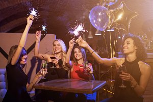 Group of female friends enjoying birthday party having fun with firework sparklers drinking alcoholic cocktails sitting around the table in restaurant