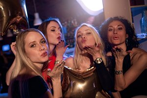 Group of attractive gorgeous girls blowing kisses looking at camera in nightclub