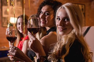 Close-up shot of positive beautiful female friends raising glasses of wine to happy event sitting in fashionable restaurant