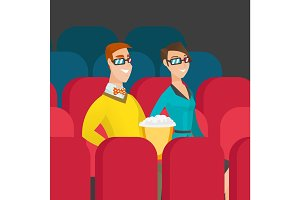 Caucasian couple watching 3D movie in the theatre.