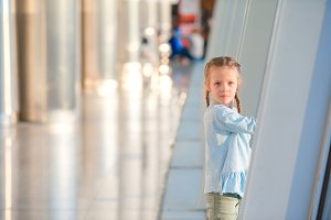 Adorable little girl in airport near big window waiting for boarding