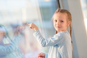 Adorable little girl in airport near big window looking at big aircraft
