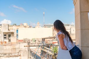 Young attractive woman on old balcony in apartment in Havana with vie of old town and houses