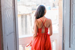Young attractive woman in red dress on old balcony in apartment in Havana