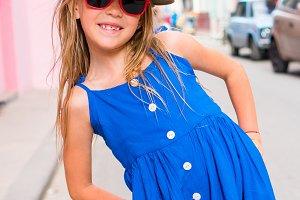 Adorable little girl in popular area in Old Havana, Cuba. Portrait of kid in old street of the city