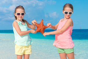 Adorable little girls with starfishes on white empty beach