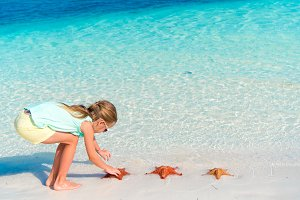Adorable little girl holding giant red starfish on white empty beach