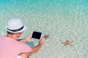 Young man with laptop on the background of turquoise ocean at tropical beach