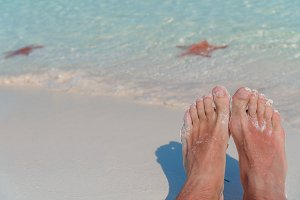 Female feet on white sandy beach. Starfish on the white sand beach in shallow water