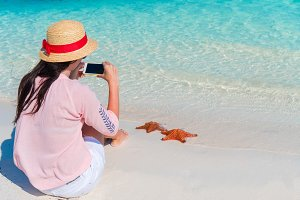 Woman with mobile phone take a photo of red starfish on the tropical beach