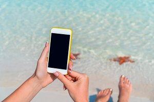 Closeup cellphone in female hands on the background of turquoise ocean at tropical beach