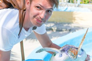 Sea turtle in the hands of tourist man in exotic reserve