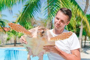 Tourist man with sea turtle in the hands in exotic reserve