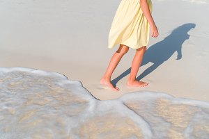 Closeup legs of little girl at shallow water
