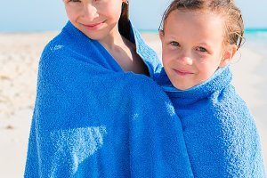 Adorable little girls together wrapped in towel at tropical beach