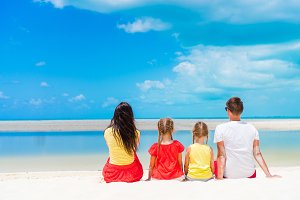 Family of four on a tropical beach together