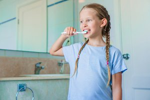Little adorable girl brushes teeth in the bathroom. Perfect snow-white smile of little girl
