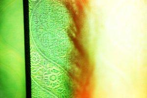Horizontal vivid green curtain with light leak bokeh background