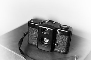 Black and white vintage camera with strap vignette bokeh backgro