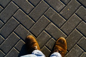 Horizontal vivid sunset boots on textured pavement background ba