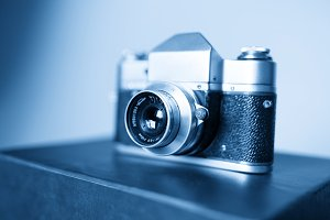 Diagonal vintage blue rangefinder camera background