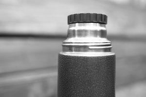 Horizontal black and white thermos bokeh background