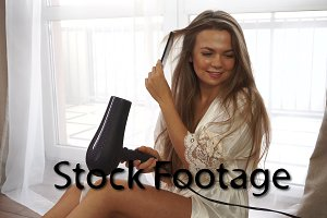 Girl dries hair with a hair dryer