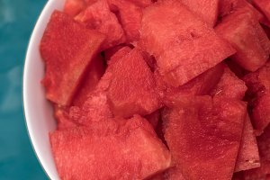 Watermelon pieces in bowl near the swimming pool.