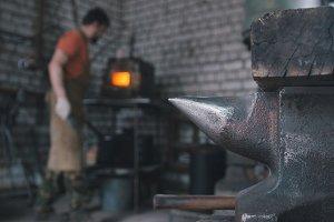 Muskular man - blacksmith in forge near furnace