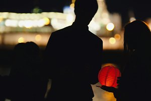 Silhouette loving couple at festival of floating Lanterns near river at night