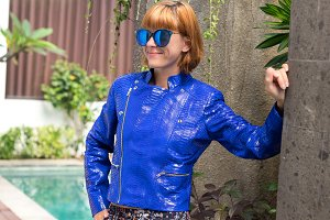 Female beauty concept. Portrait of fashionable young girl in blue luxury snakeskin python jacket and sunglasses posing near the swimming pool. Perfect hair. Outdoor villa shot.