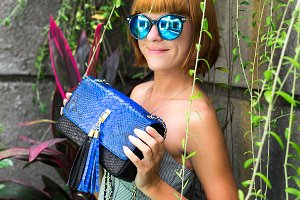 Stylish fashion girl, beautiful young woman posing with luxury snakeskin python handbag and sunglasses. Tropical island Bali, Indonesia.