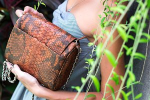 Stylish fashion girl, beautiful young woman posing with luxury snakeskin python handbag. Tropical island Bali, Indonesia.