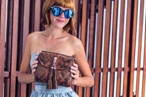 Stylish fashion girl, beautiful young woman posing with luxury snakeskin python handbag and sunglasses. Tropical island Bali, Indonesia.