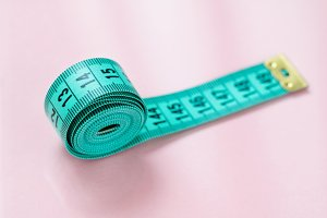Close-up of blue measuring tape on the pink background