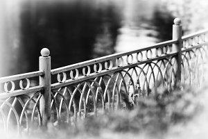 Horizontal diagonal black and white fence in park bokeh vignette