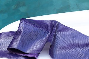 Genuine python snakeskin leather, snake skin, texture background. Swimming pool on a background.