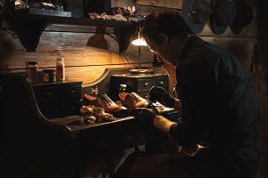 Handsome man shoemaker at footwear workshop.