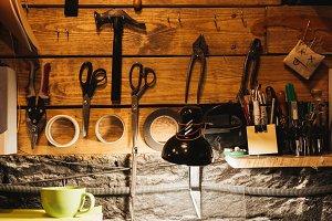 Ynstruments on wooden wall at footwear workshop.