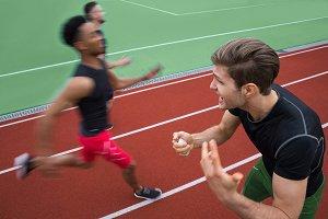 Trainer screaming near young multiethnic athlete men run
