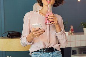 Young pretty girl holding mobile phone and drinking smoothie