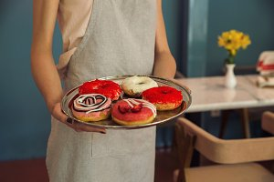 Young woman in apron holding tray with donuts