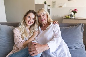 Smiling granddaughter and grandmother sitting together