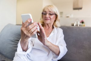 Beautiful senior woman in eyeglasses using a smartphone