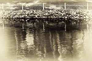 Horizontal sepia vignette park fence near lake background
